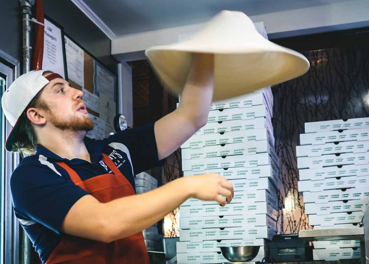 a male chef spinning pizza dough in a pizzeria