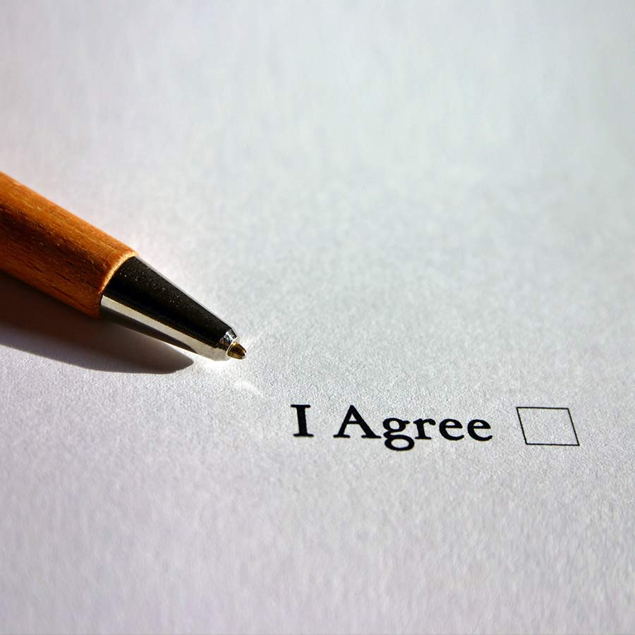 """a pen laying next to an unchecked check box titled """"I Agree"""""""