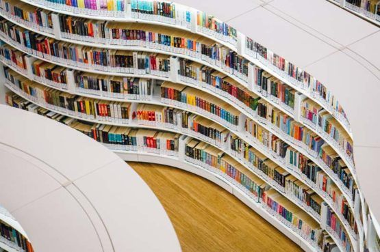 A large, curved library bookcase holding colourful books