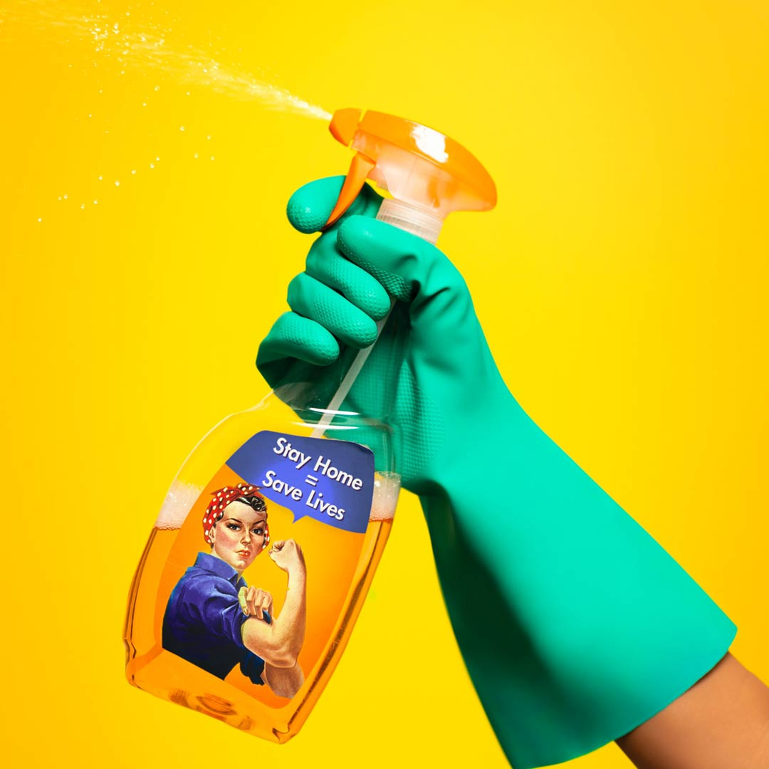 a hand with a rubber glove holding a bottle of spray cleaner